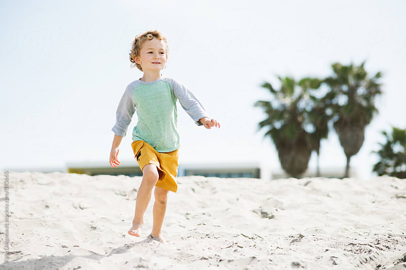 Young boy excitedly running down beach in the summer. by Kate Daigneault for Stocksy United