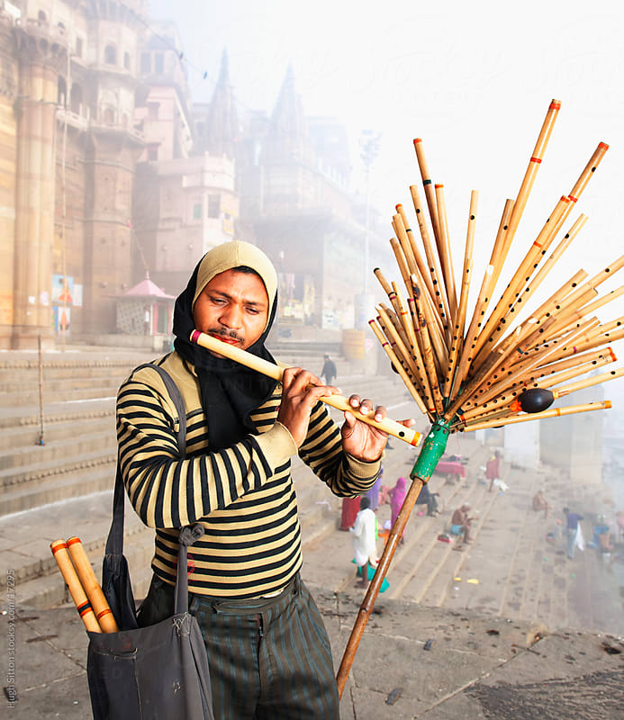 Flute salesman standing by ghat. Varanasi. India by Hugh Sitton for Stocksy United