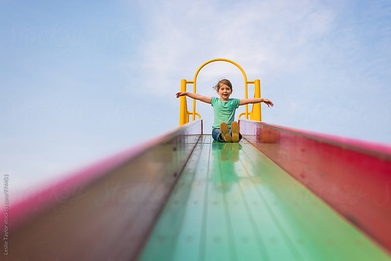 Girl Happily Going Down A Slide by Leslie Taylor for Stocksy United