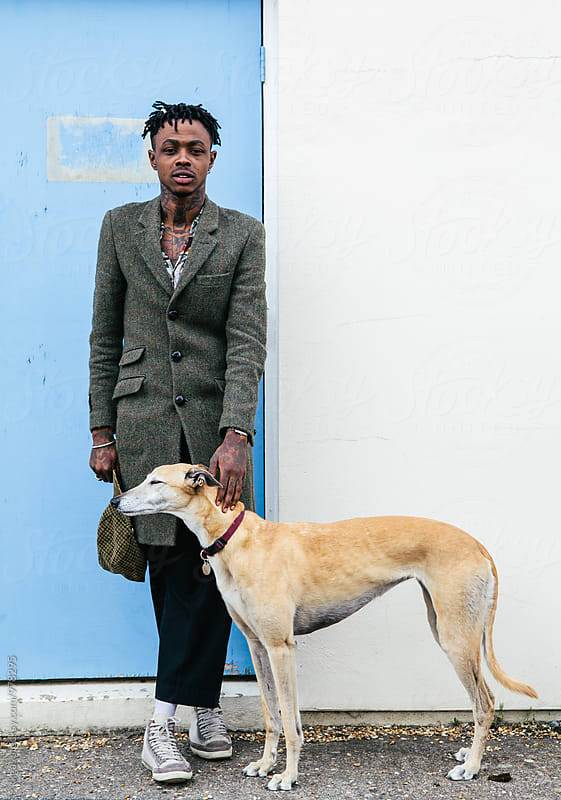 Portrait of a tattooed black man with a greyhound by kkgas for Stocksy United