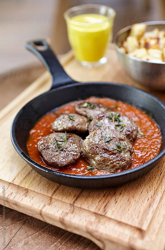 Meatballs with tomato sauce and thyme by Paperclip Images for Stocksy United