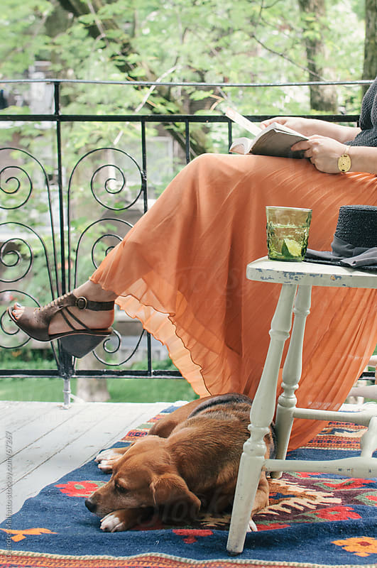 woman reads book and dog sleeps on balcony by Deirdre Malfatto for Stocksy United