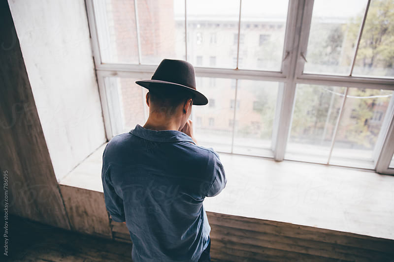 Man dressed in hat looking at window by Andrey Pavlov for Stocksy United