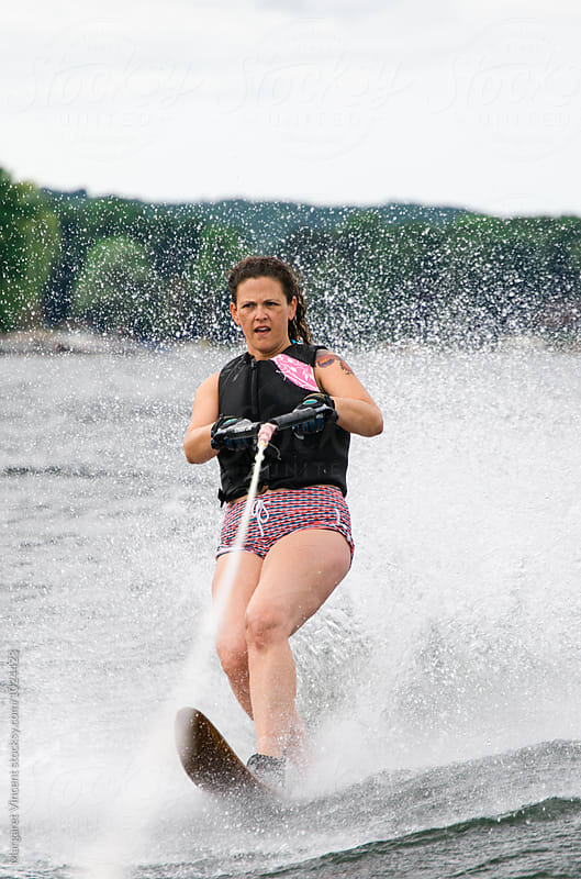woman water skis with spray by Margaret Vincent for Stocksy United