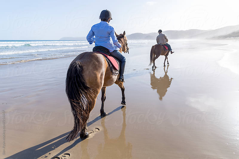 Rear view of senior male and female riding horse back in shorebreak by Ben Ryan for Stocksy United