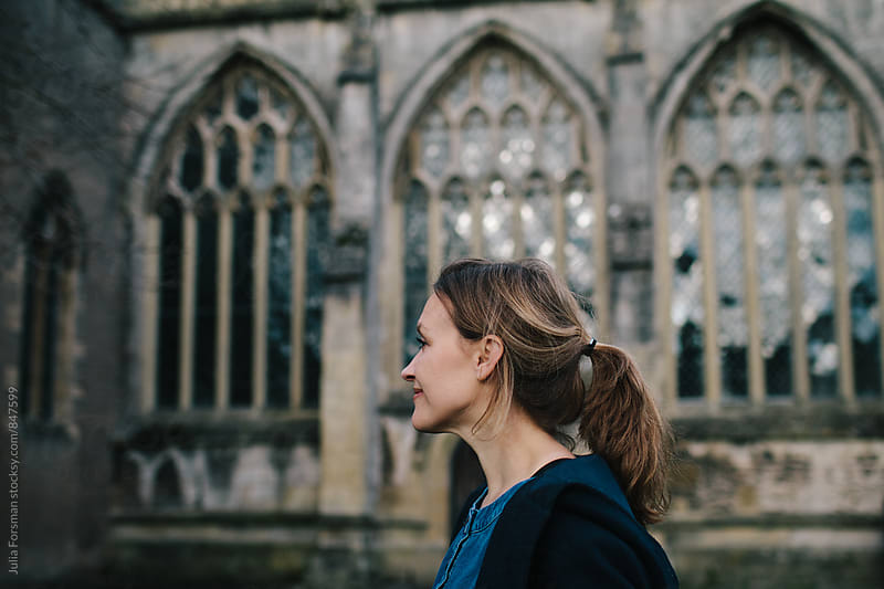 A woman walks past a church. by Julia Forsman for Stocksy United