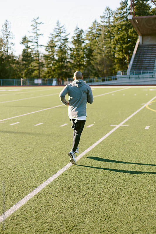 Athletic Man Running Lines On Turf Field For Warmup Before Workout by Luke Mattson for Stocksy United