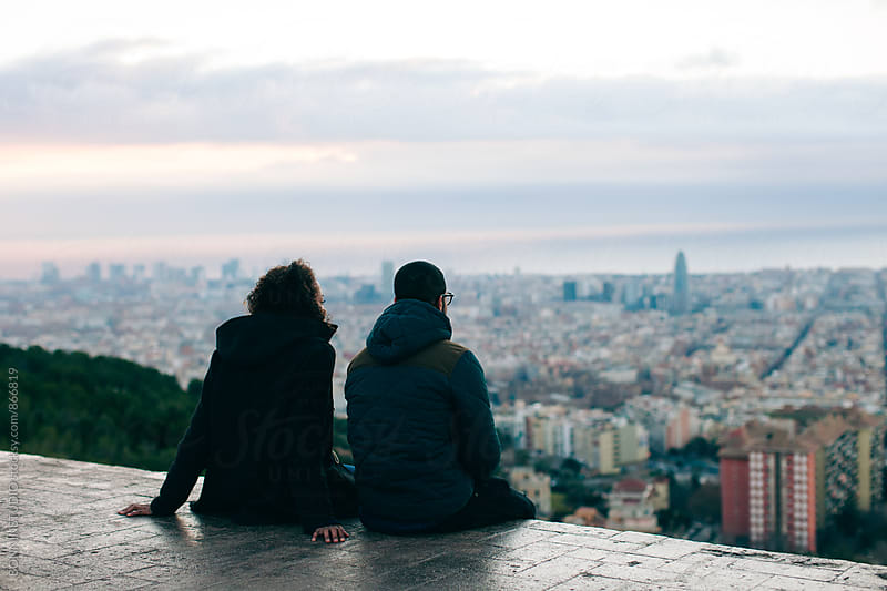 Back view of couple sitting above city at sunrise. by BONNINSTUDIO for Stocksy United