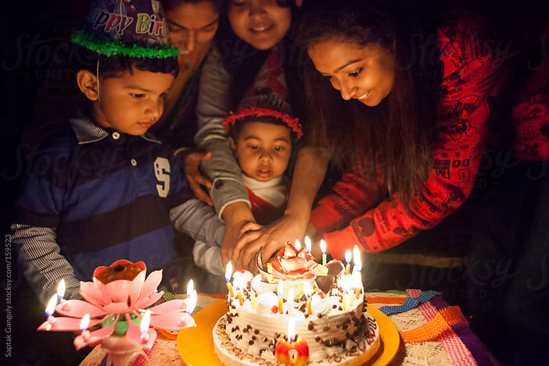 Toddler cutting her birthday cake with the help of her elders by Saptak Ganguly for Stocksy United