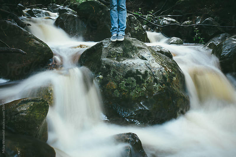 Person standing on a rock in the middle of a fast flowing stream by Micky Wiswedel for Stocksy United