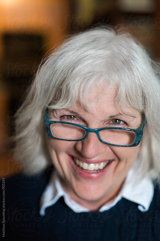 Smiling woman with grey hair and glasses by Matthew Spaulding for Stocksy United