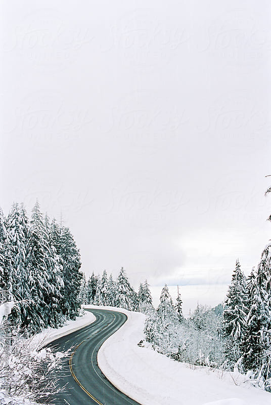 Curvy road in snow by Daniel Kim Photography for Stocksy United