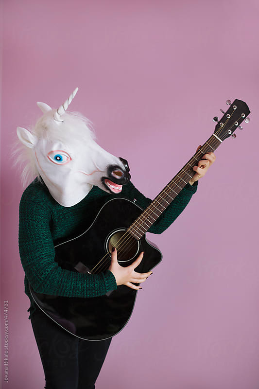 Woman in a unicorn mask playing guitar by Jovana Rikalo for Stocksy United
