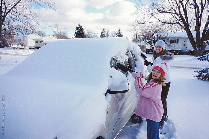 Mother and Daughter clearing snow from vehicle.  by Hugh Sitton for Stocksy United
