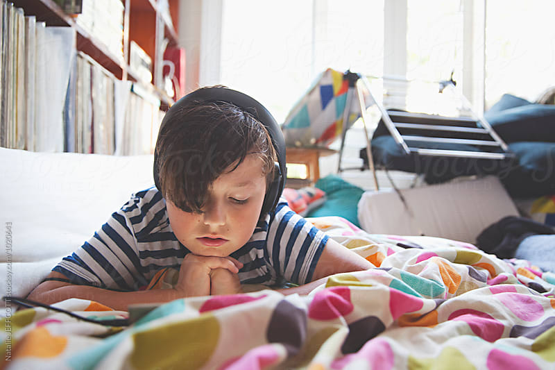 A young boy lies on bed with headphones using a tablet device by Natalie JEFFCOTT for Stocksy United
