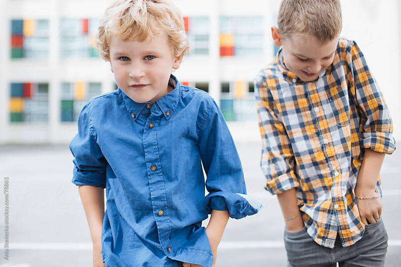 Two boys standing with hands in pockets in front of a school by Ania Boniecka for Stocksy United