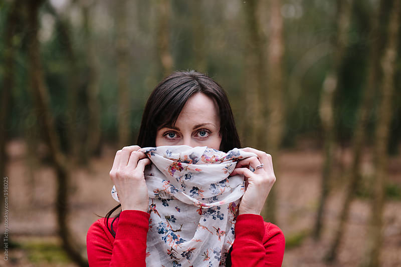 Woman holding scarf in front of her face by Gabriel Tichy for Stocksy United