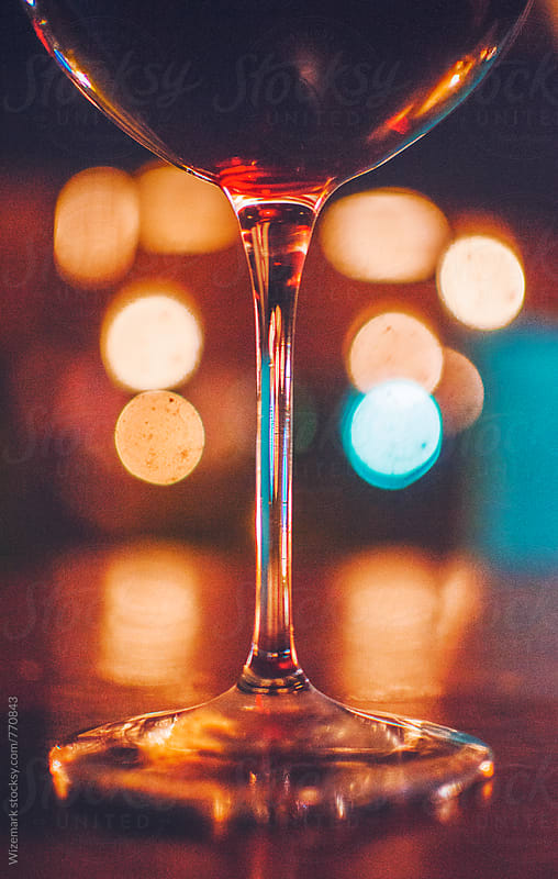 Glass of red wine on the table at night by Srdjan Kirtic for Stocksy United