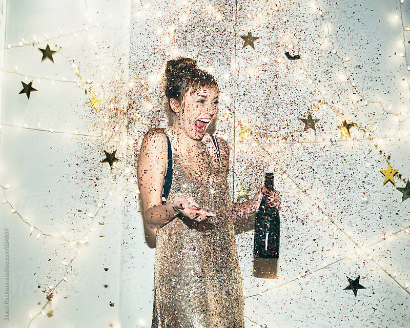 Young woman being showered in glitter by Shaun Robinson for Stocksy United