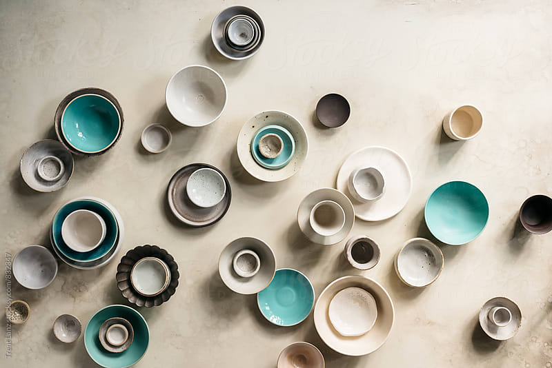 Modern handmade collection of ceramic cups, bowls plates collection on plaster table  by Trent Lanz for Stocksy United