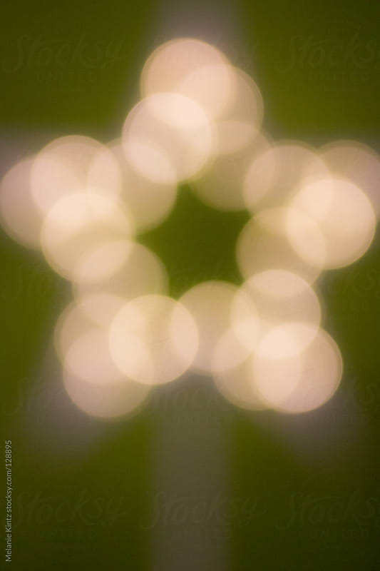 Blurred star shape before green background by Melanie Kintz for Stocksy United
