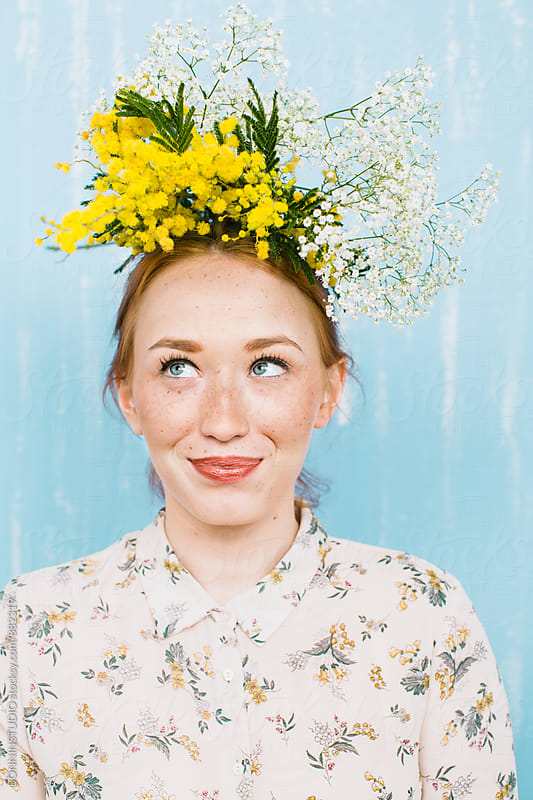 Young ginger woman with flowers on head smiling. by BONNINSTUDIO for Stocksy United