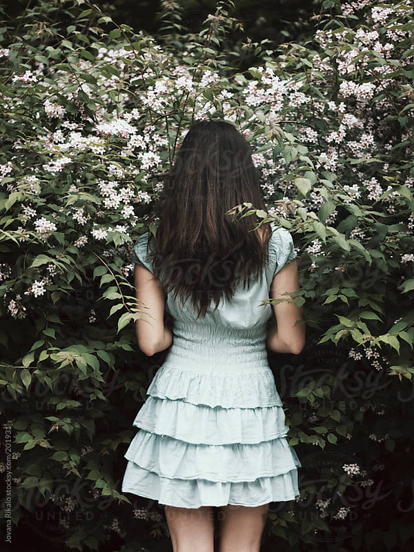 Back view of a young woman standing in front of a bush by Jovana Rikalo for Stocksy United