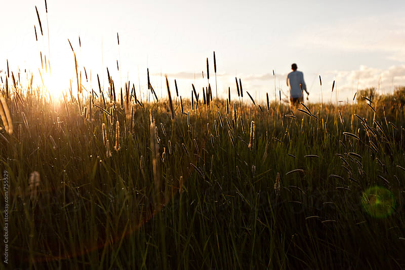 Man in field with fishing rod by Andrew Cebulka for Stocksy United