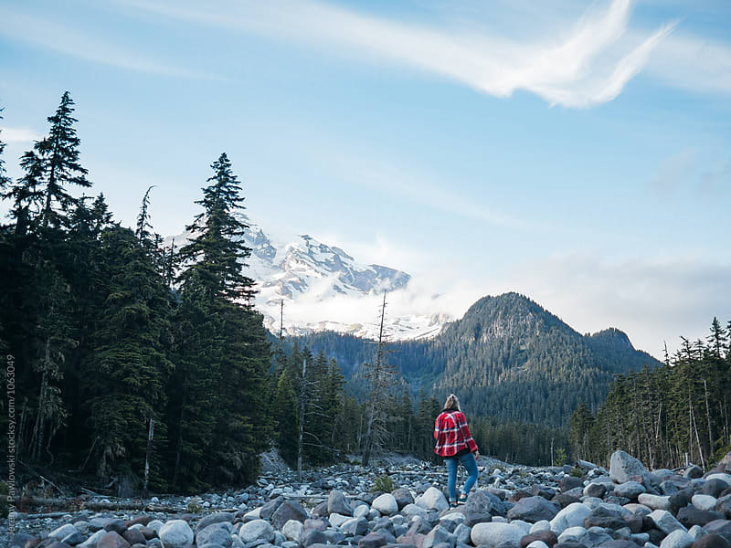 Hipster female in flannel shirt hiking on rocks toward mountain by Jeremy Pawlowski for Stocksy United