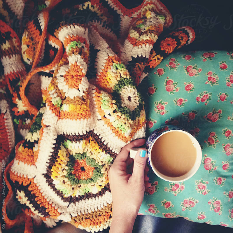 cozy cup of coffee with pillow and afghan by Kristin Rogers Photography for Stocksy United