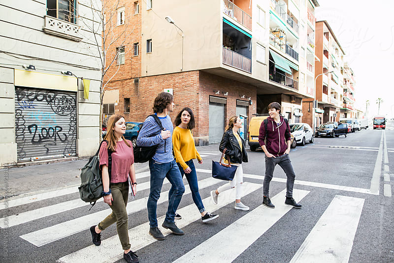 Group of teen friends crossing the street. by BONNINSTUDIO for Stocksy United