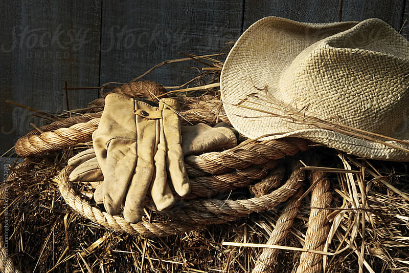 Hat and leather gloves on hay by Sandra Cunningham for Stocksy United