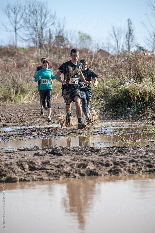 Mud Runners Enter a Water Hazzard by Brian McEntire for Stocksy United