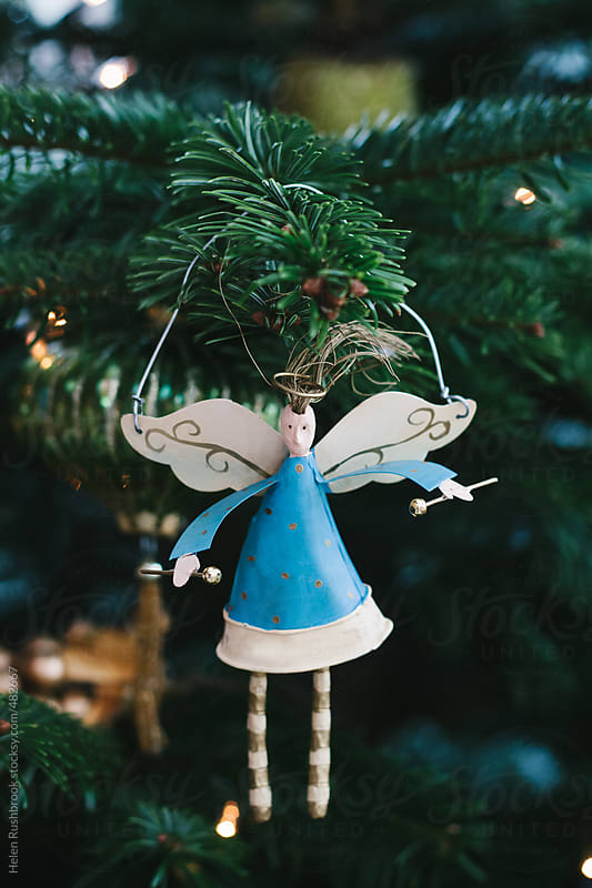 A drumming angel Christmas decoration hanging on a Christmas tree. by Helen Rushbrook for Stocksy United