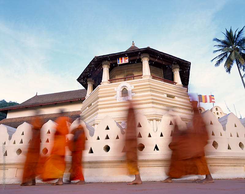 Buddhist monks in orange robes walking past Temple of the Tooth. Kandy. by Hugh Sitton for Stocksy United