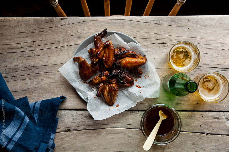 Casual table setting with spicy chicken wings and glasses of beer by Nadine Greeff for Stocksy United