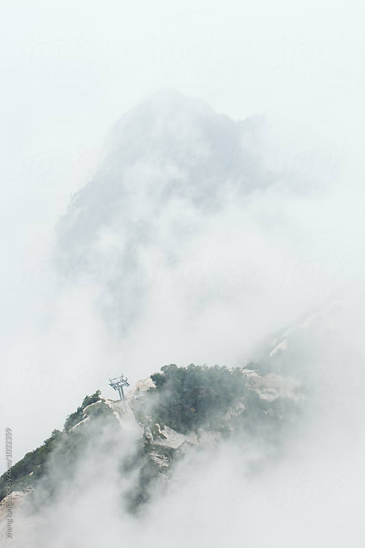 Cableway in Huashan Mountain in the fog by zheng long for Stocksy United