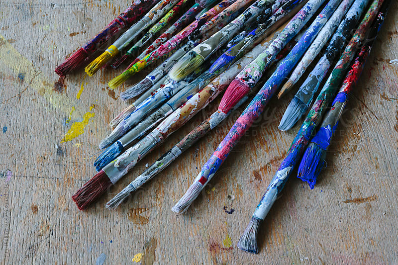 Used paint brushes with multi-coloured handles lying on a classroom table by Paul Phillips for Stocksy United