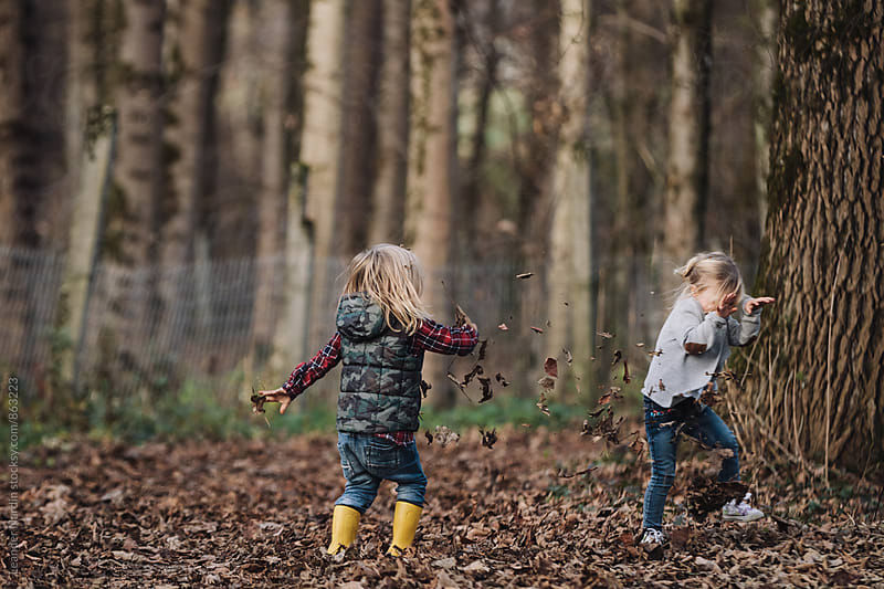 little boy and girl throwing around with foliage in a forest by Leander Nardin for Stocksy United