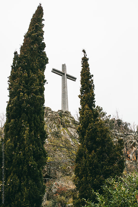 Cross monument between cypress trees by Alejandro Moreno de Carlos for Stocksy United