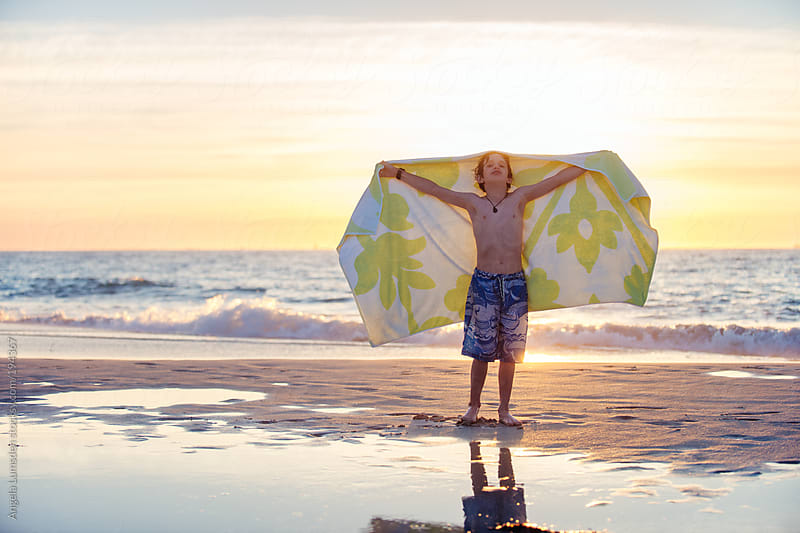 Boy with a towel at the beach at sunset by Angela Lumsden for Stocksy United