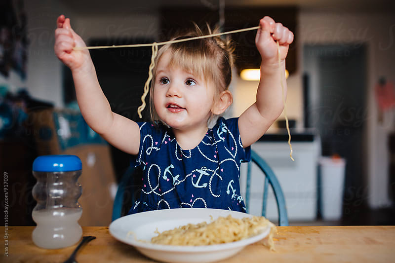 Toddler girl playing with noodle by Jessica Byrum for Stocksy United