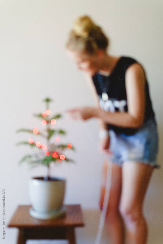 Defocused image of teen girl decorating a small Norfolk Pine tree for Christmas by Jacqui Miller for Stocksy United