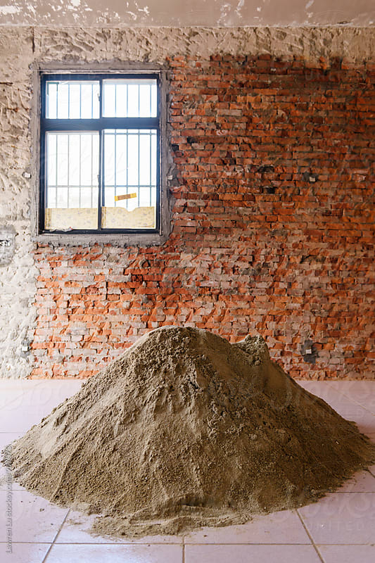 Room in construction house with brick wall and pile of sand by Lawren Lu for Stocksy United
