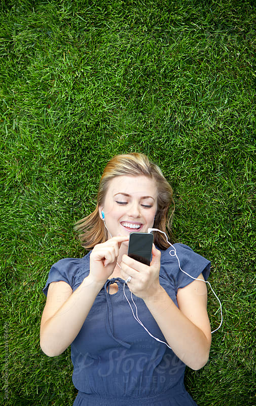 Grass: Woman Picks Playlist to Listen To by Sean Locke for Stocksy United