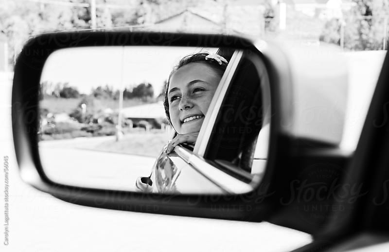 Smiling  girl with her head out the window of the car by Carolyn Lagattuta for Stocksy United