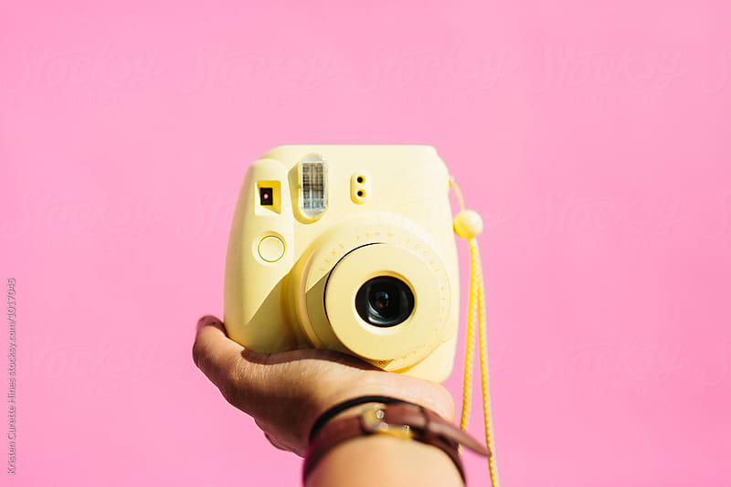 A hand holding out a yellow instax polaroid camera.  by Kristen Curette Hines for Stocksy United