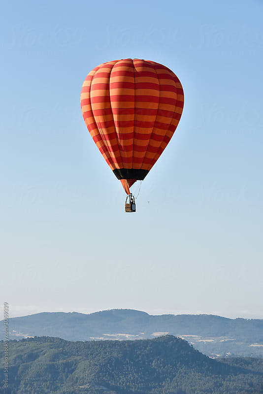 Alone hot air balloon flying over a blue sky by Bisual Studio for Stocksy United