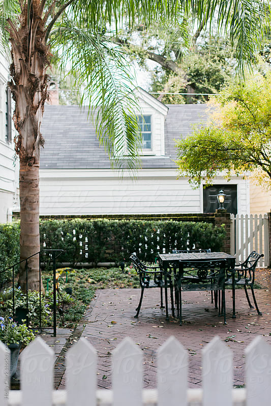 Ornate table and chairs on a brick patio in a quaint garden by Holly Clark for Stocksy United