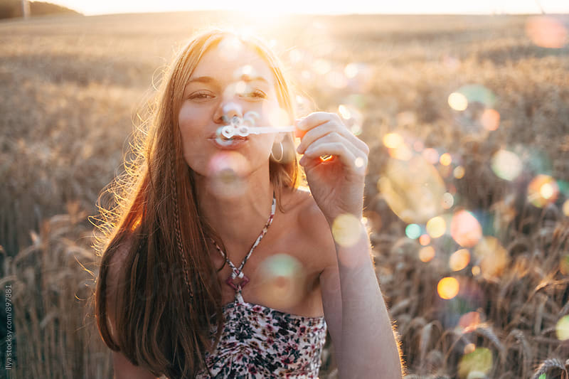 Young woman in summer dress blowing soap bubbles on sunset  by Ilya for Stocksy United